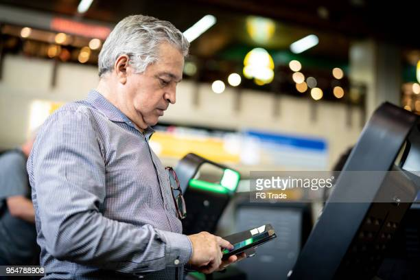Mature businessman making Online check-in