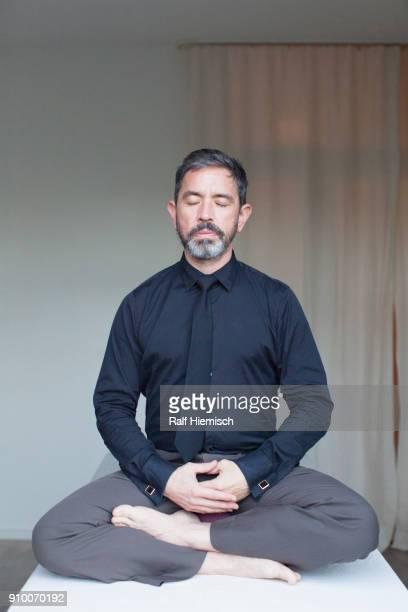 Mature businessman meditating at home
