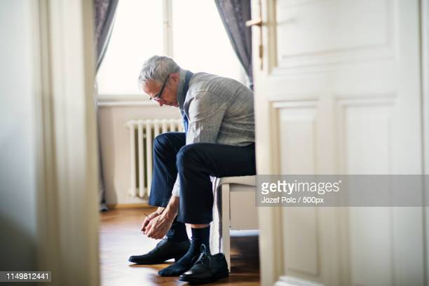 mature businessman on a business trip sitting in a hotel room, tying shoelaces - tied up stock pictures, royalty-free photos & images