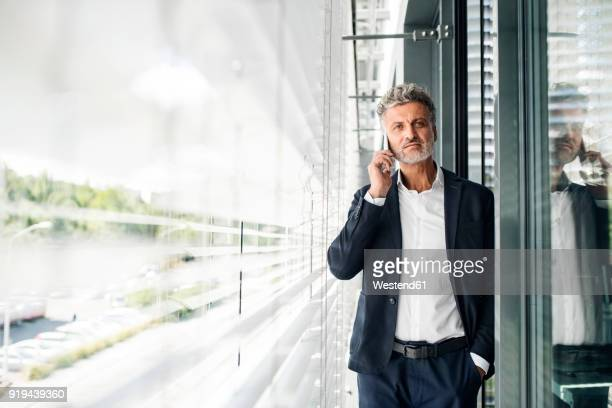 Mature businessman on cell phone at outside sunblind