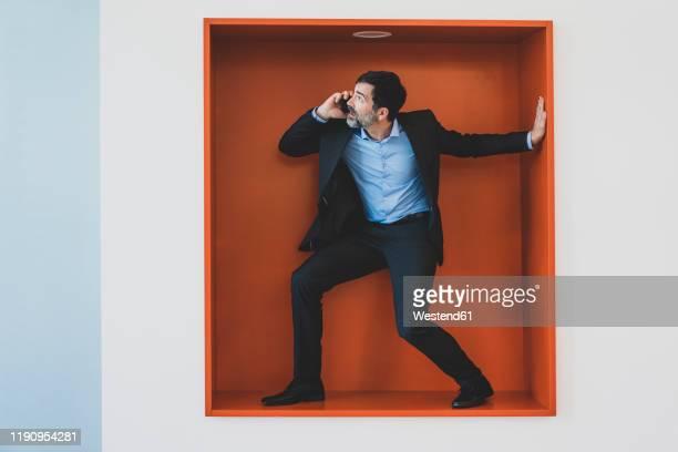 mature businessman on cell phone caught in a niche - nauw stockfoto's en -beelden