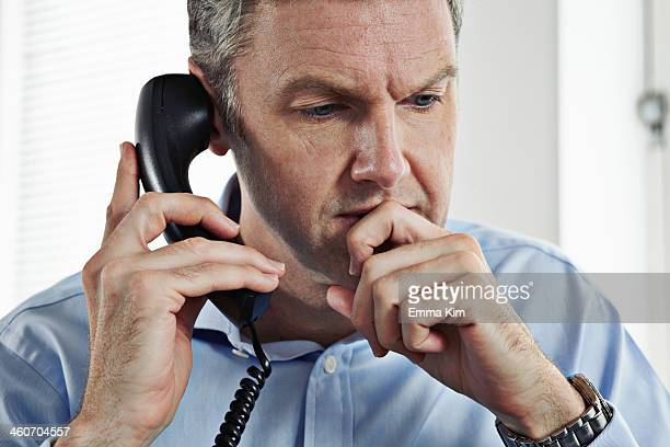Mature businessman on landline phone
