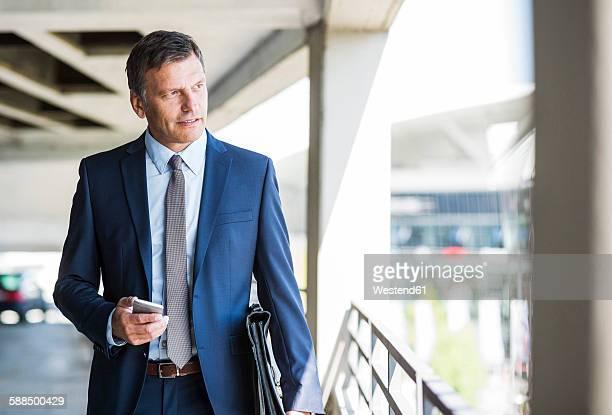 Mature businessman on park deck using mobile phone
