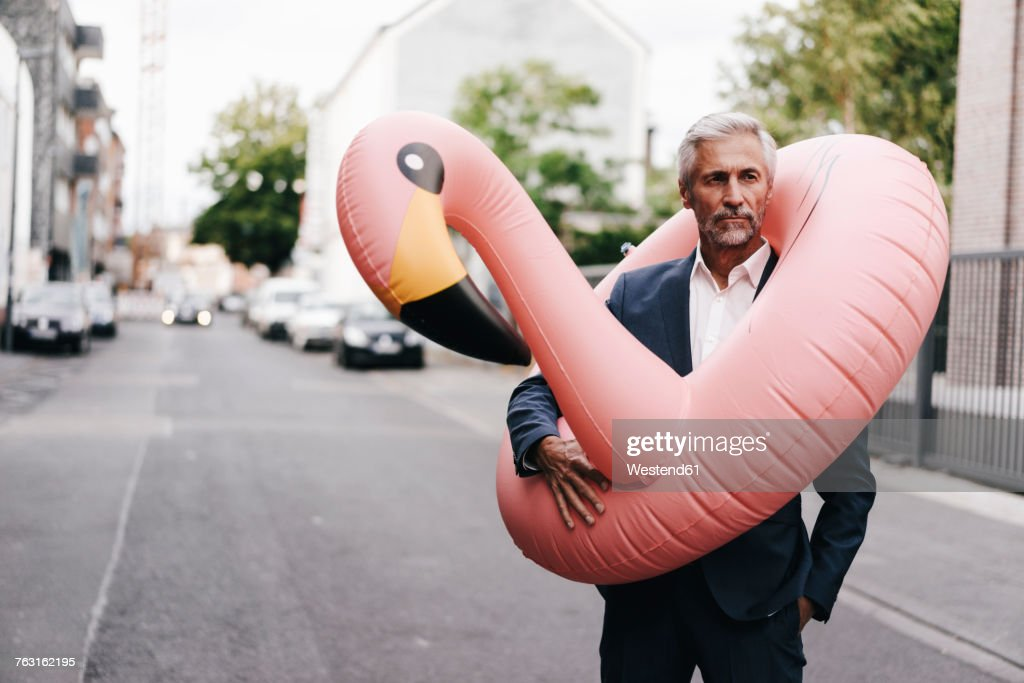 Mature businessman on the street with inflatable flamingo : Stock Photo