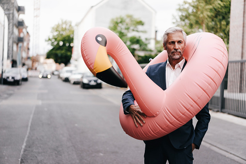 Mature businessman on the street with inflatable flamingo - gettyimageskorea