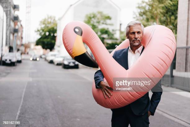 mature businessman on the street with inflatable flamingo - opstand stockfoto's en -beelden