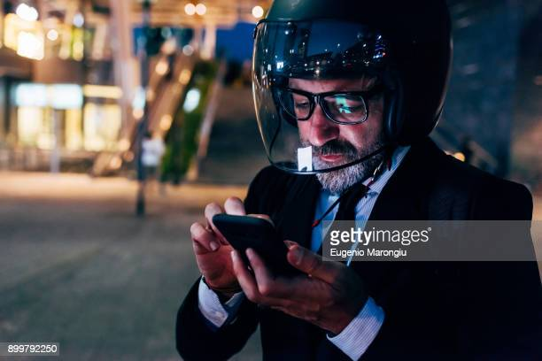 mature businessman outdoors at night, wearing motorcycle helmet, using smartphone - バイクヘルメット ストックフォトと画像