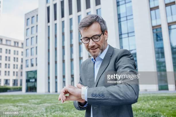 mature businessman outdoors checking his smartwatch - guardare verso il basso foto e immagini stock