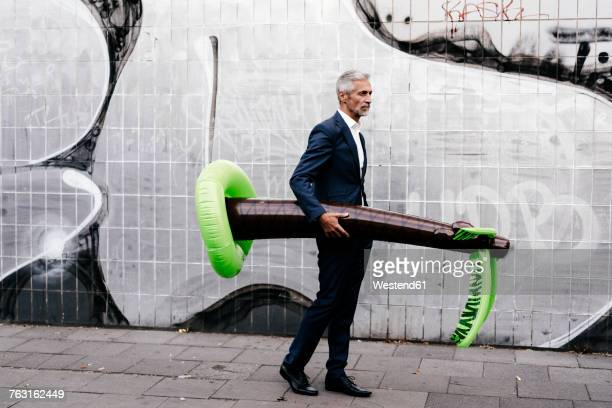 mature businessman outdoors with inflatable palm tree - artistic product stock pictures, royalty-free photos & images