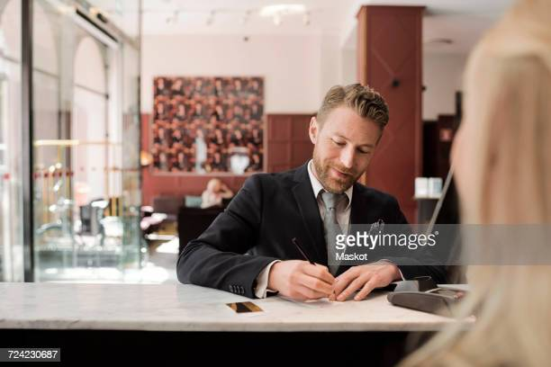 Mature businessman paying through credit card at hotel reception