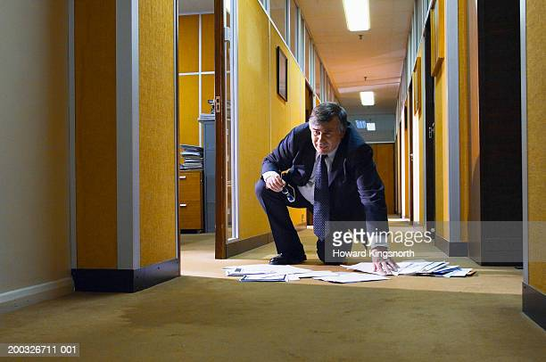 Mature businessman picking up papers from floor in office