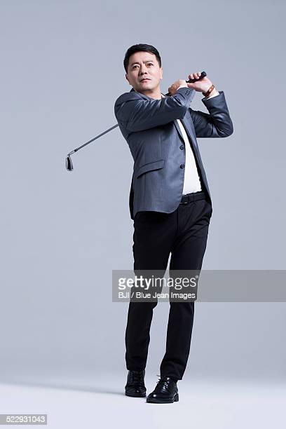 Mature businessman playing golf
