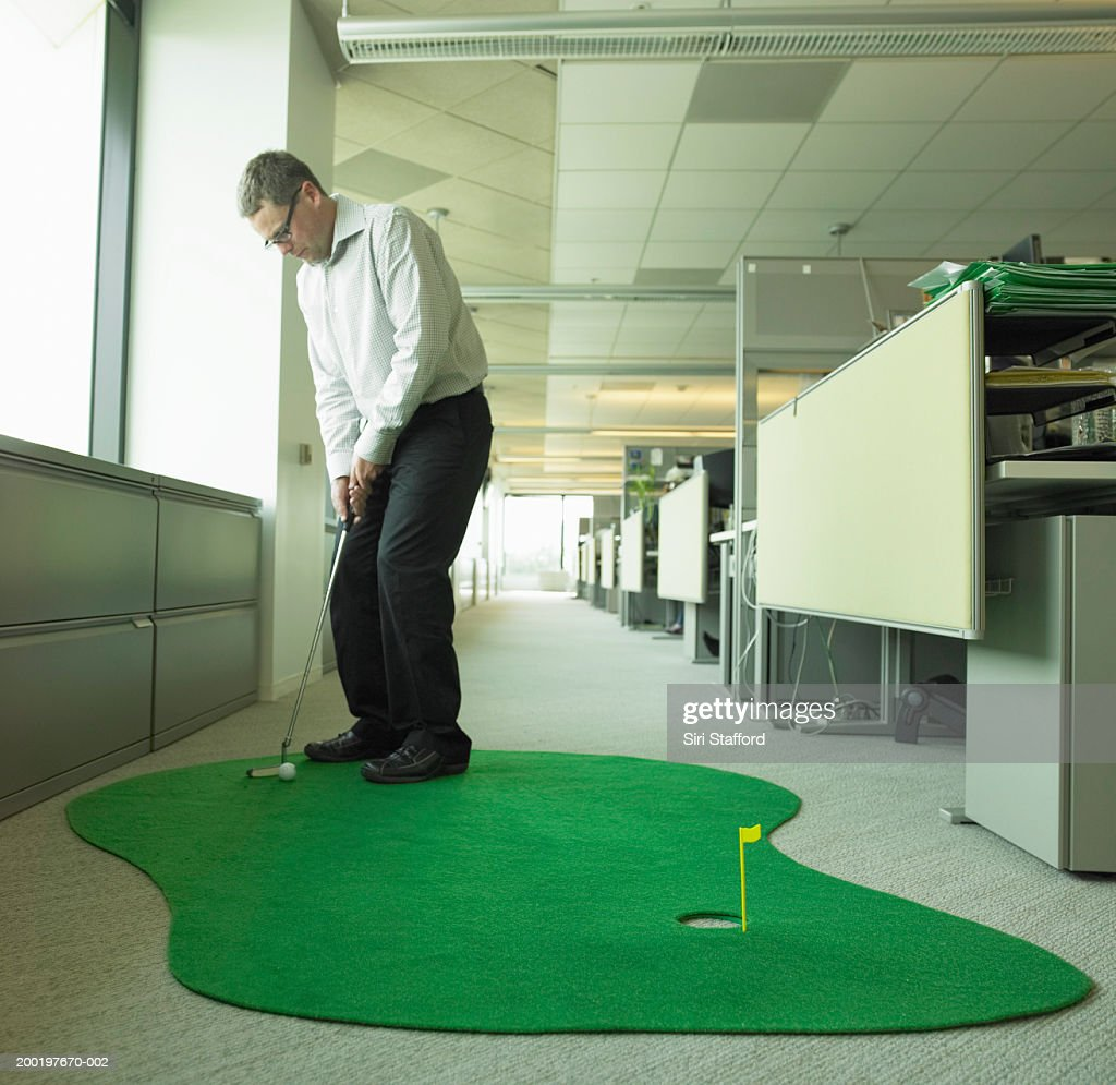 Office Pictures For Walls Golf: Mature Businessman Playing Miniature Golf In Office Stock