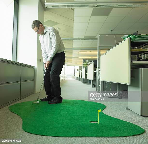 Mature businessman playing miniature golf in office