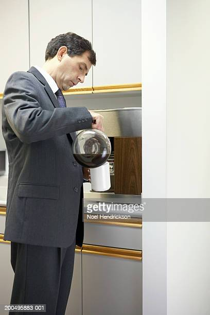 Mature businessman pouring cup of coffee in office kitchen, side view