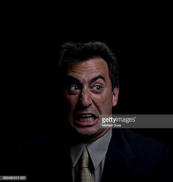 mature businessman pulling face, close-up - grimacing stock pictures, royalty-free photos & images