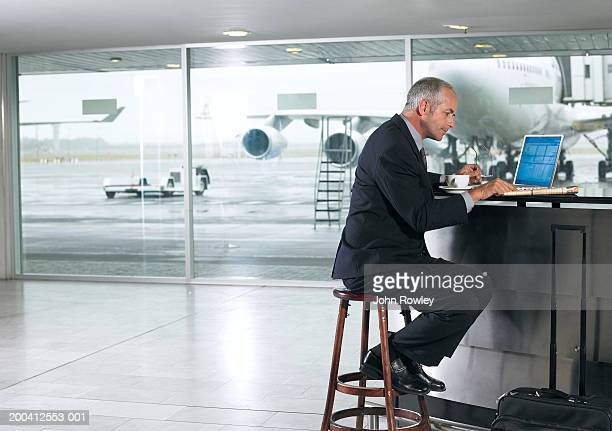 mature businessman reading newspaper by laptop in airport, side view - socialite stock pictures, royalty-free photos & images