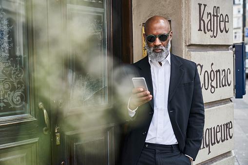 Mature businessman reading smartphone messages - gettyimageskorea
