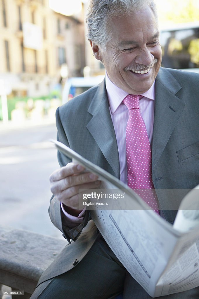 Mature Businessman Reads a Newspaper, Laughing : Stock Photo