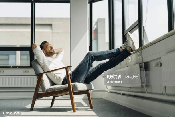 mature businessman relaxing at the window in empty office - lässige kleidung stock-fotos und bilder