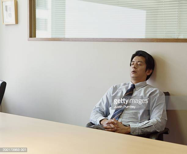 Mature businessman relaxing in chair at conference table, eyes closed