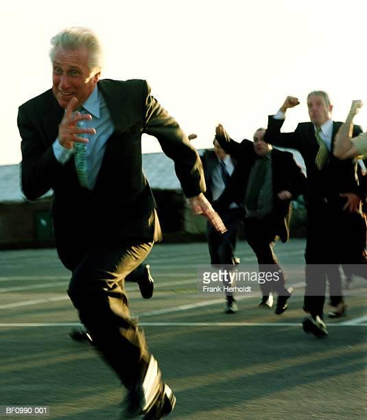 mature businessman running from crowd outdoors (blurred motion) - zwaaien gebaren stockfoto's en -beelden