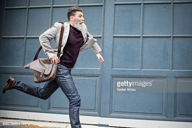 mature businessman rushing to work - dringendheid stockfoto's en -beelden