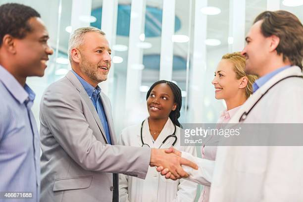 成熟したビジネスマンに手を振る医師、病院を通過します。