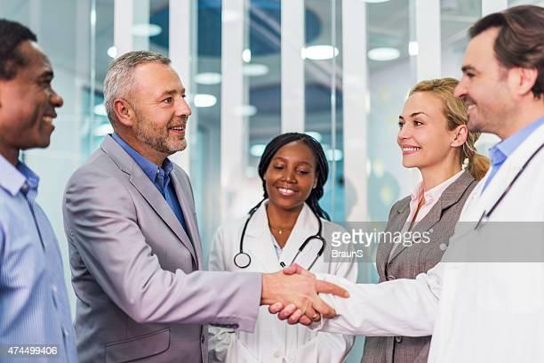 Maduro hombre de negocios estrechándose las manos con un doctor en el hospital.