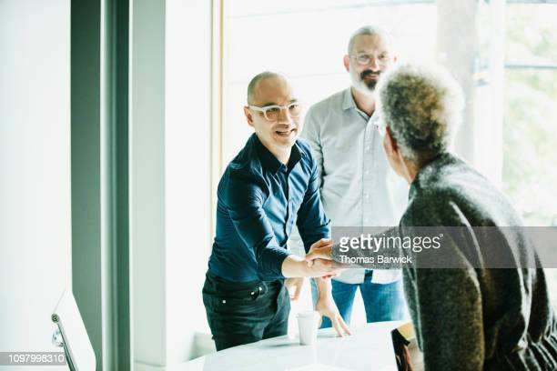 mature businessman shaking hands with client before meeting in office conference room - good news stock pictures, royalty-free photos & images