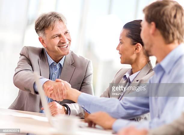 Maduro hombre de negocios estrechándose las manos con su compañero de la oficina.
