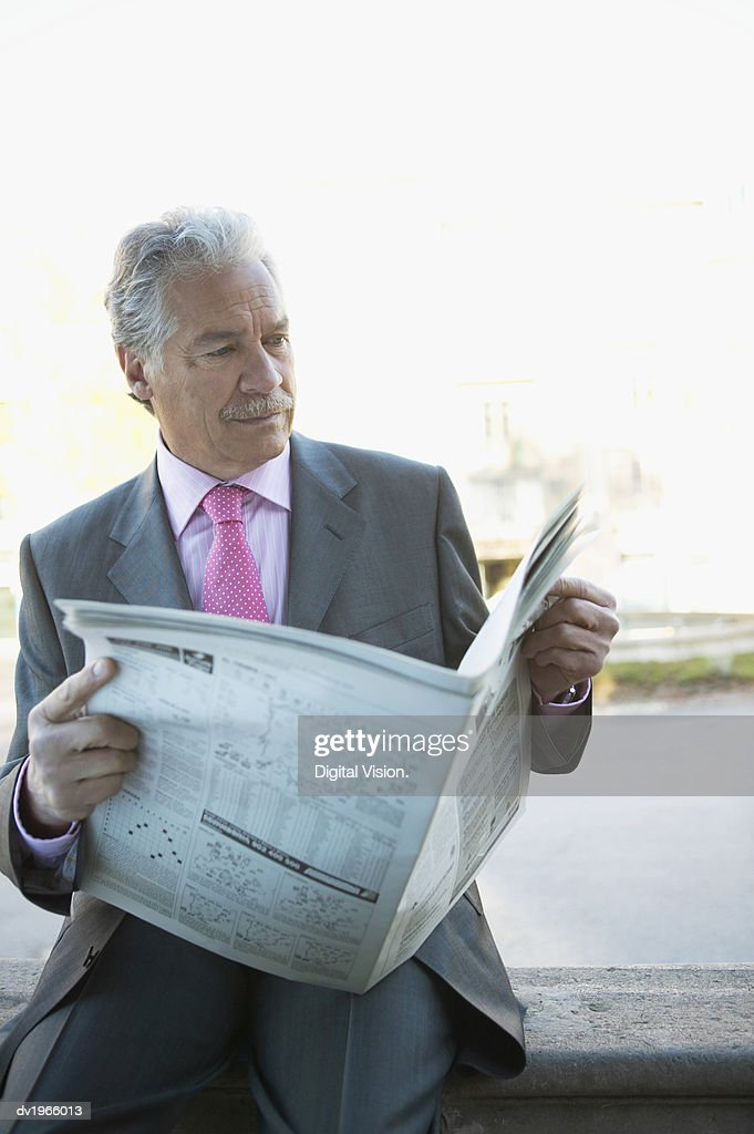 Mature Businessman Sits on a Wall, Reading a Newspaper : Stock Photo