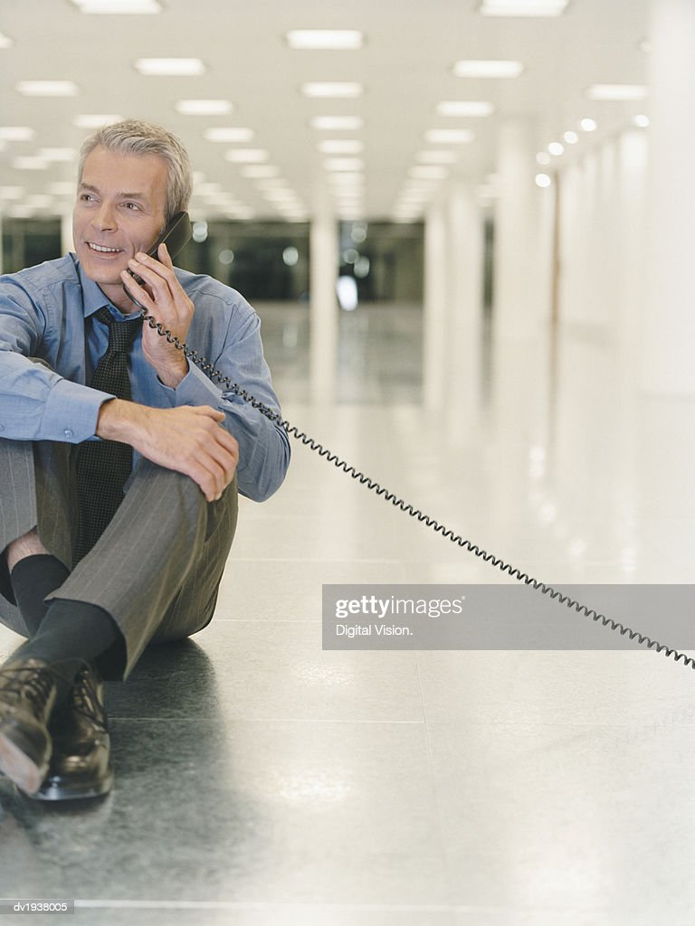 Mature Businessman Sits on the Floor of an Empty Office, Talking on the Phone : Stock Photo
