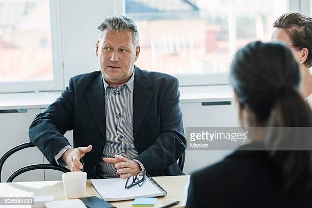 Mature businessman sitting and explaining coworkers at office