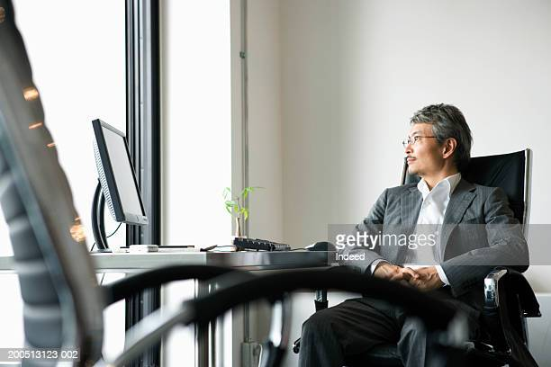 Mature businessman sitting at desk, looking out window, side view