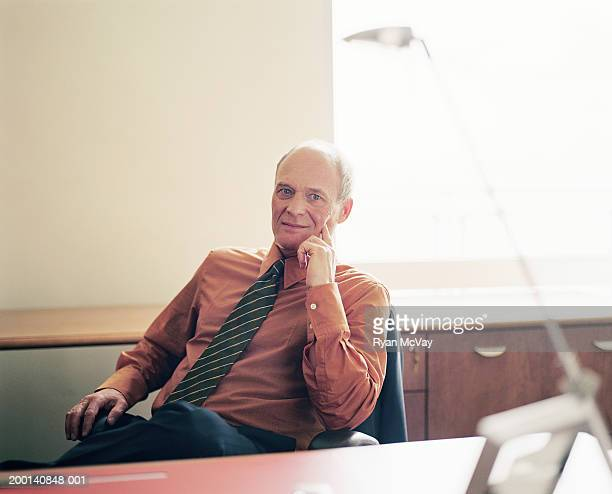 Mature businessman sitting at desk, portrait