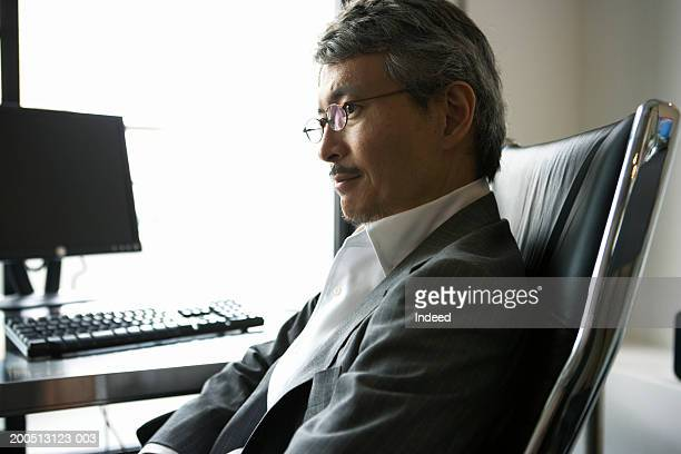 Mature businessman sitting at desk, side view