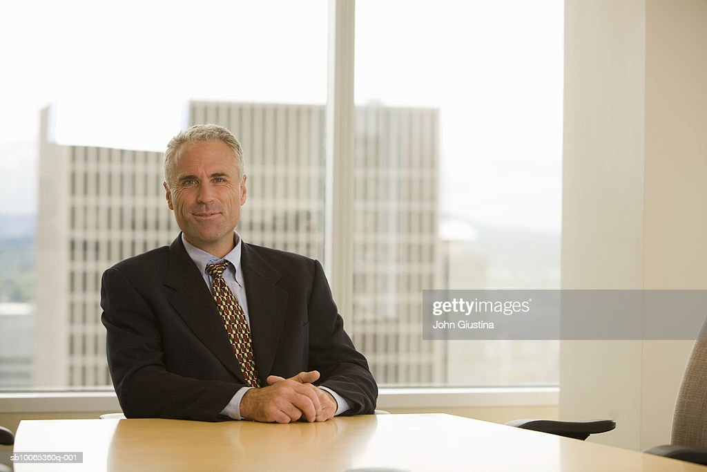 Mature businessman sitting at desk, smiling, portrait : Foto stock