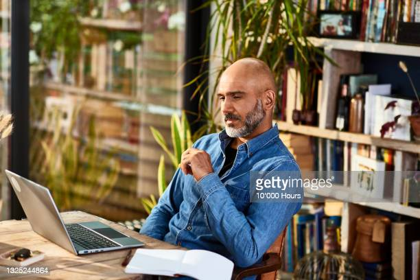 mature businessman sitting at home watching laptop - contemplation stock pictures, royalty-free photos & images