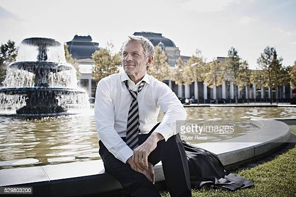 Mature businessman sitting at pond