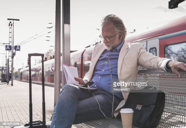 mature businessman sitting at train station with cell phone, earbuds and notebook - bahnreisender stock-fotos und bilder