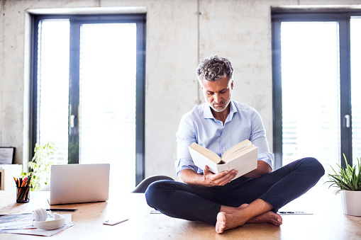 Mature businessman sitting barefoot on desk in office reading a book - gettyimageskorea