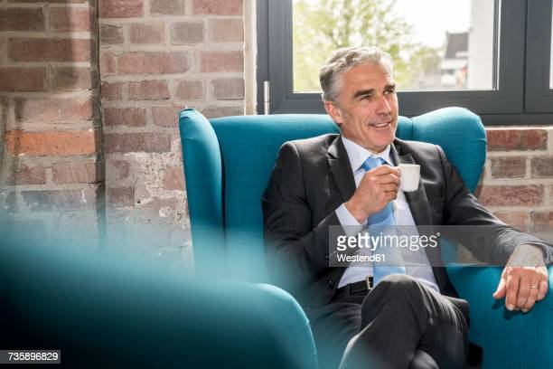 Mature businessman sitting in arm chair, drinking coffee