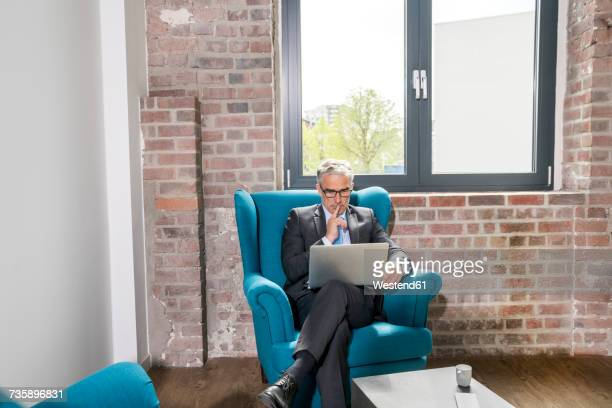 Mature businessman sitting in arm chair, using laptop