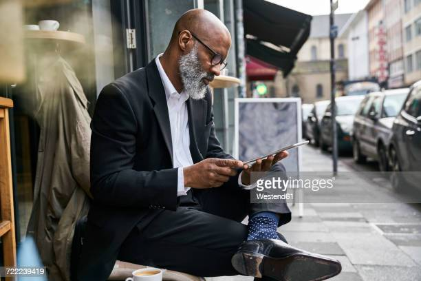 mature businessman sitting in cafe using digital tablet - portable information device stock-fotos und bilder