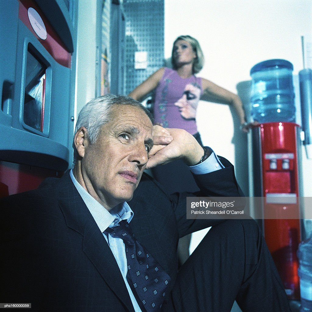 Mature businessman sitting in chair, young woman behind posing. : Stockfoto