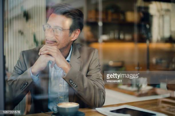 mature businessman sitting in coffee shop, smiling - da cintura para cima imagens e fotografias de stock