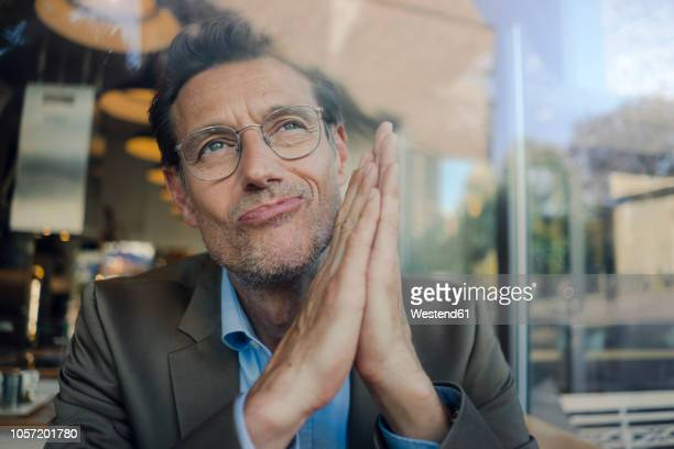 mature businessman sitting in coffee shop, smiling - tevreden stockfoto's en -beelden