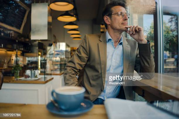 mature businessman sitting in coffee shop, smiling - encuadre cintura para arriba fotografías e imágenes de stock