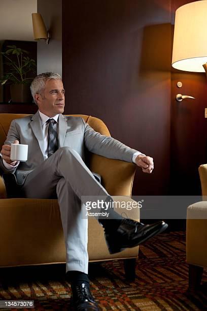 mature businessman sitting in private lounge - piernas cruzadas fotografías e imágenes de stock